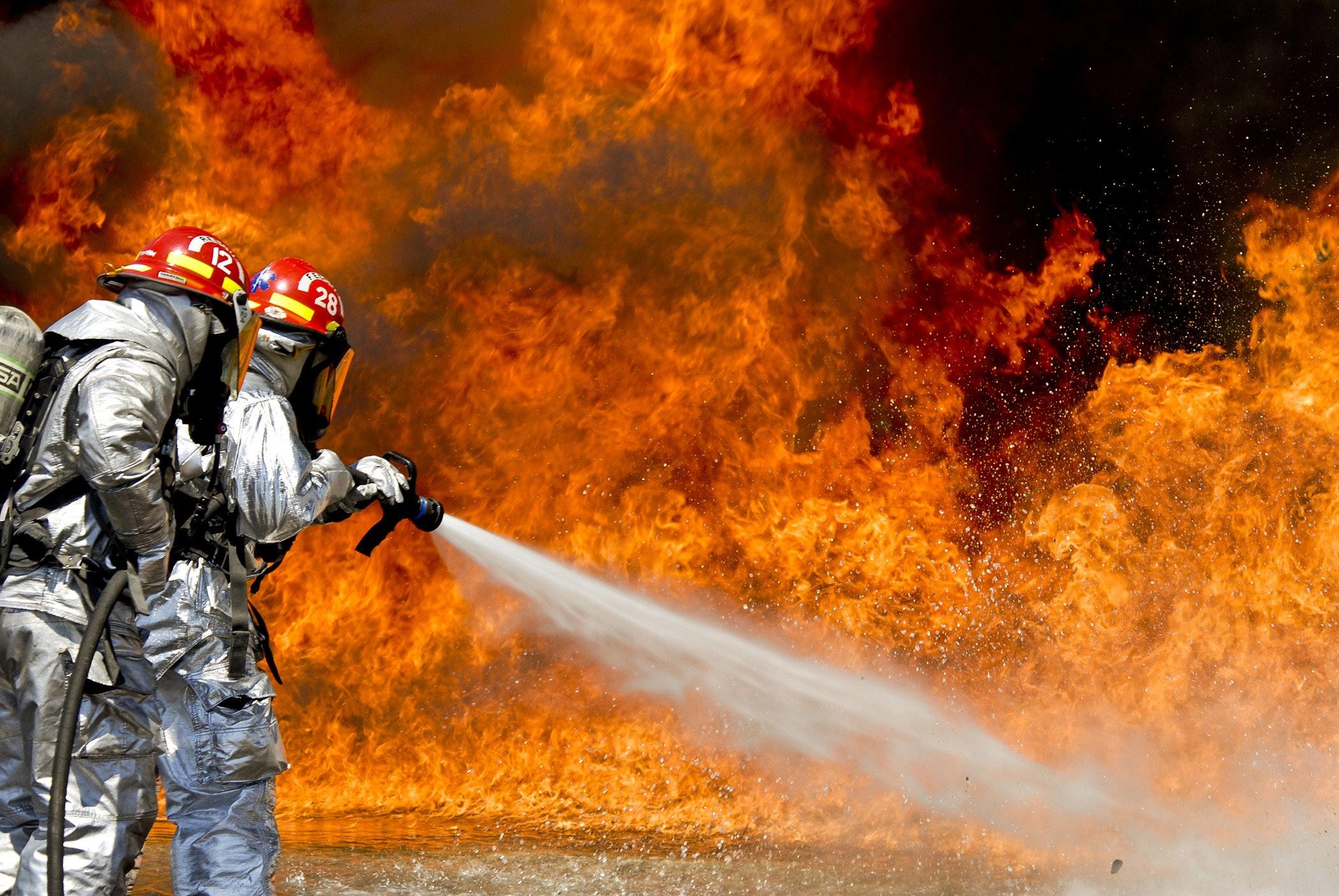 两名身穿发光西装的消防员正在用水灭火